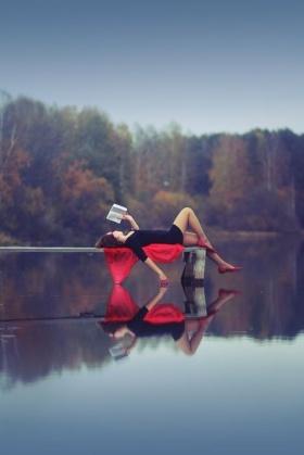 woman reading by a lake